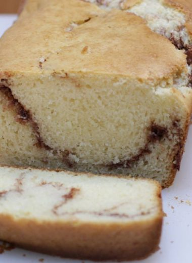 cinnamon quick bread sliced on a white cutting board