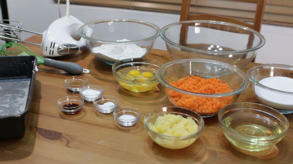 several glass bowls holding ingredients for making moist carrot cake, including pineapple, eggs, oil, carrots, flour, etc.