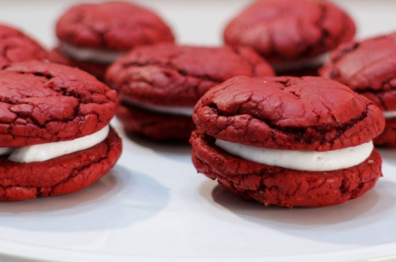 Red velvet whoopie pies on a white cake pedestal