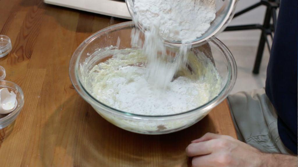 Hand adding a bowl of flour to the Belgian sugar waffles dough