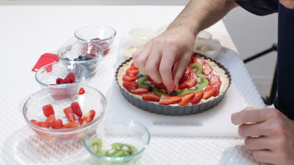 Hand placing fruit to complete the fruit tart on a table.
