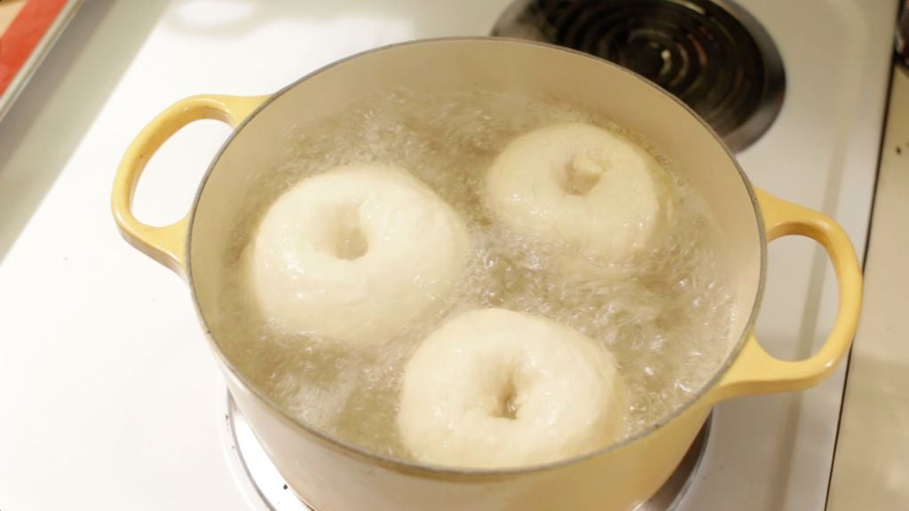 Three homemade bagels boiling in a pot of water