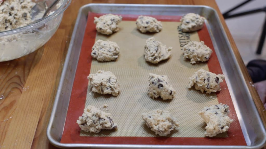Eggless chocolate chip cookie dough on a baking sheet sitting on a wooden table.