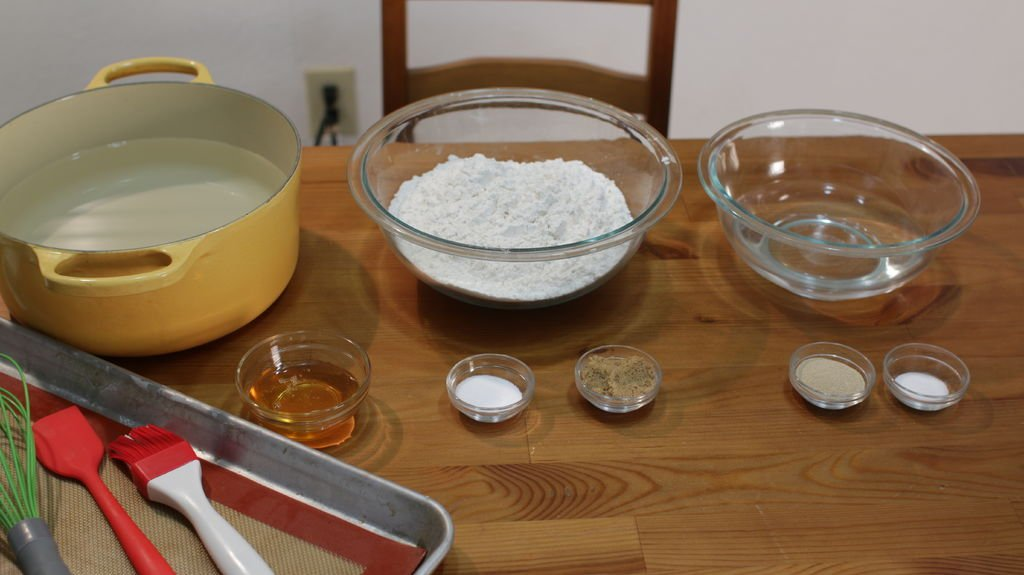 ingredients to make bagels in glass bowls on a wooden table