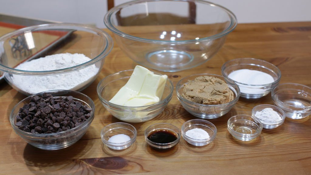 tools and ingredients in glass bowls on a wooden table for making chocolate chip cookies, including flour, butter, sugar, etc.