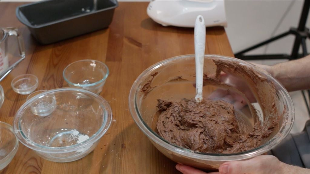 Finished chocolate bread batter in a large glass bowl on a wooden table.