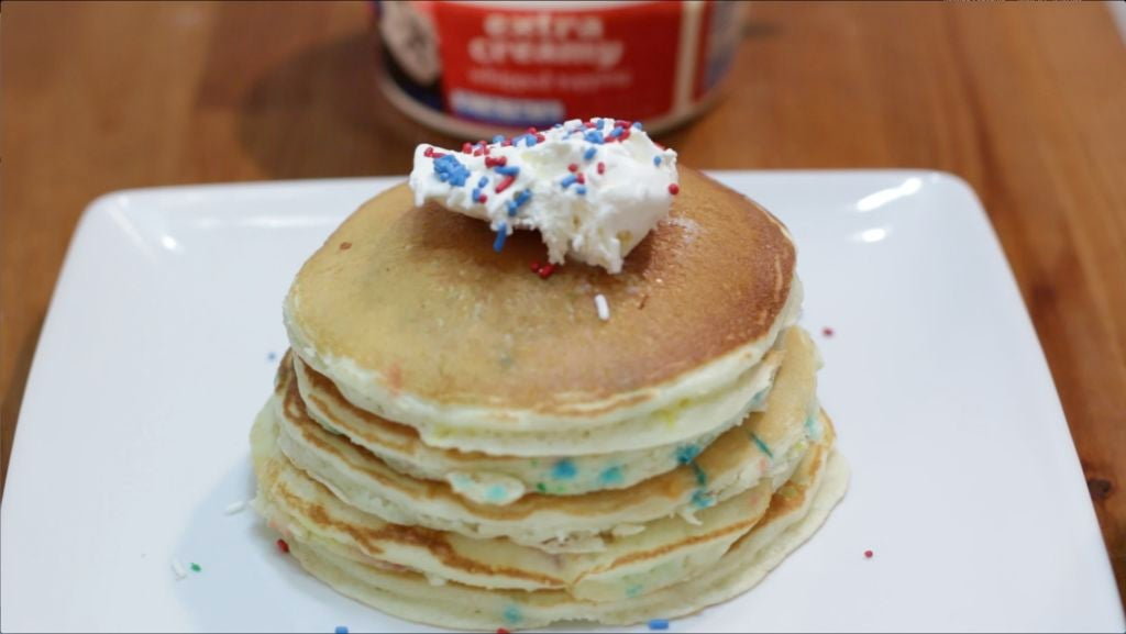Stack of funfetti cake mix pancakes on a plate with whip cream and sprinkles