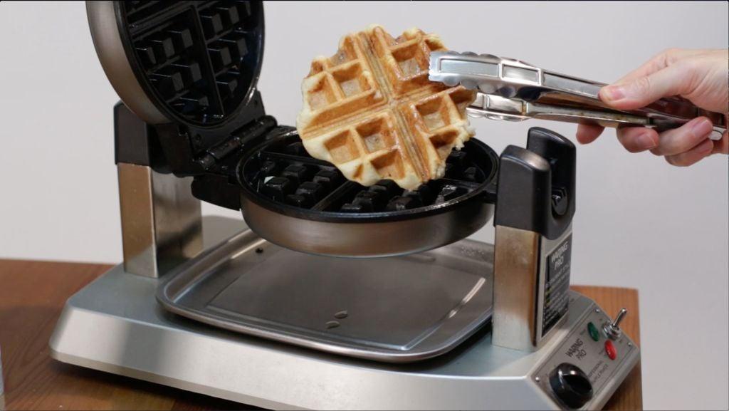 Tongs grabbing a fully cooked sugar waffle