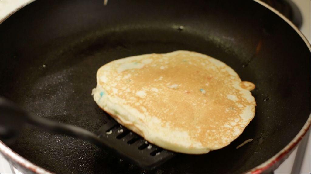 Spatula flipping a funfetti cake mix pancake.