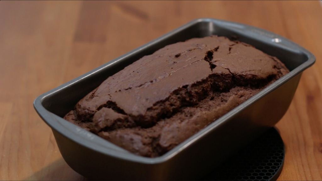 Freshly baked chocolate bread in a bread loaf pan on top of a wooden table.