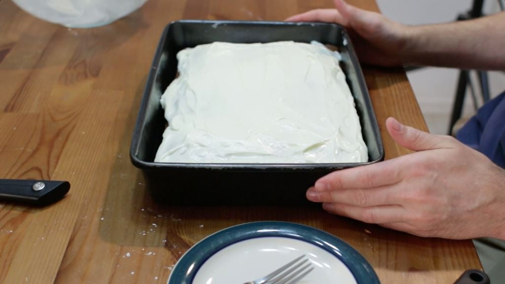 Finished frosting moist carrot cake in a 13x9 inch baking pan on a wooden table.