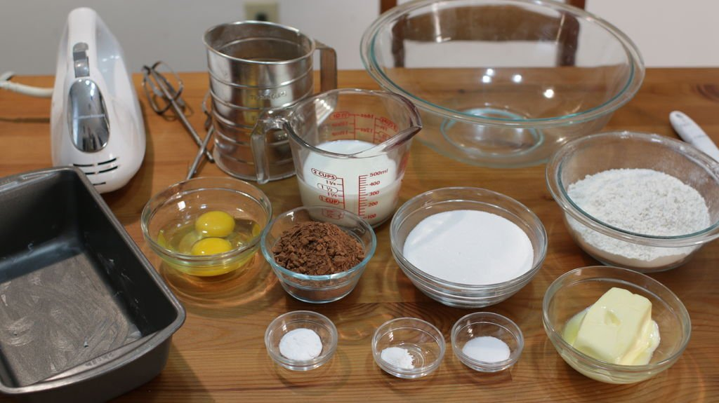 Ingredients and tools to make chocolate bread on a wooden table, in glass bowls.