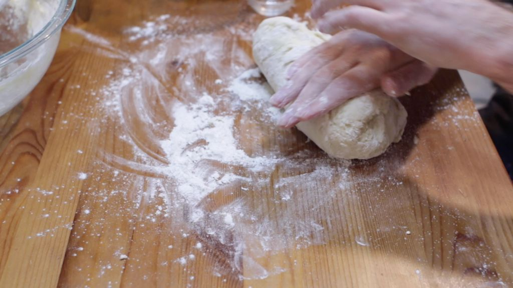 Hand kneading the king cake dough on a floured wooden table.