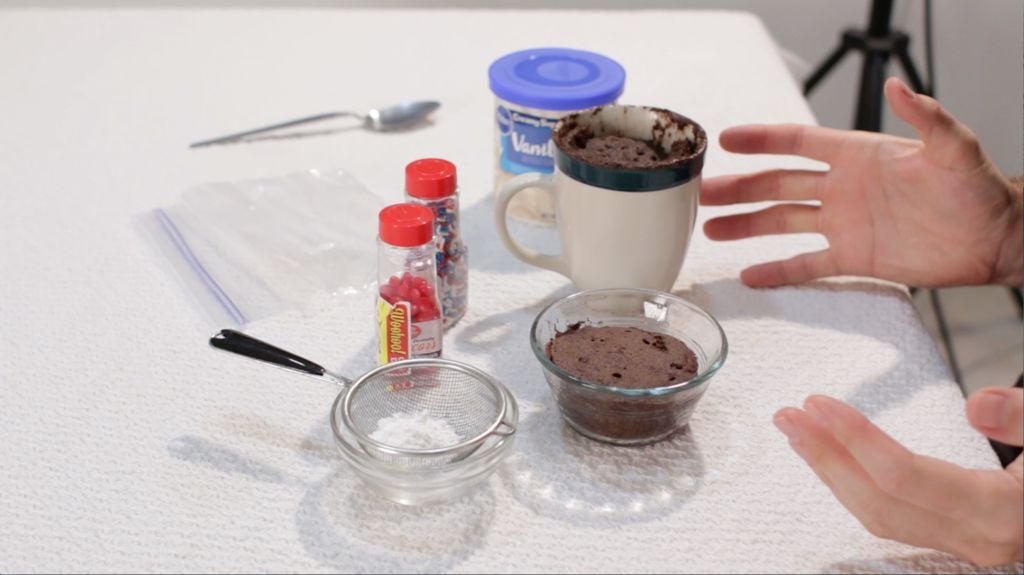chocolate mug cake and bowl cakes sitting on a table with white table cloth.
