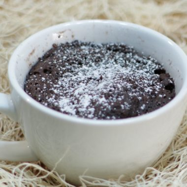chocolate cake in a white mug with powdered sugar