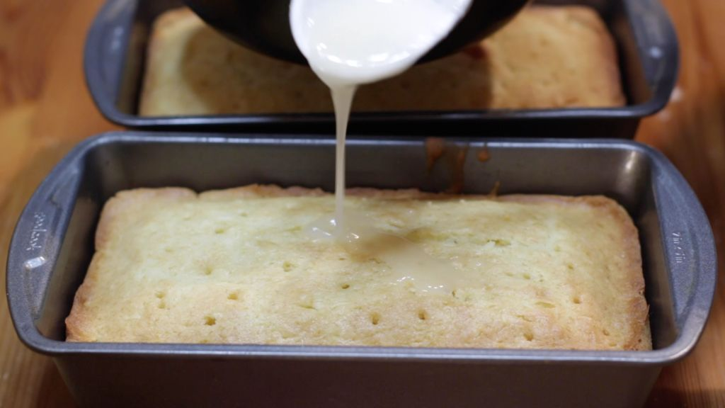 Hot glaze being poured all over the top of the coconut bread