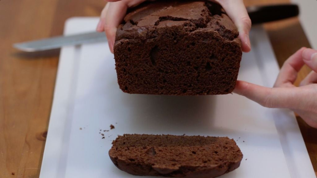 Hands holding a loaf of chocolate bread which has been sliced.