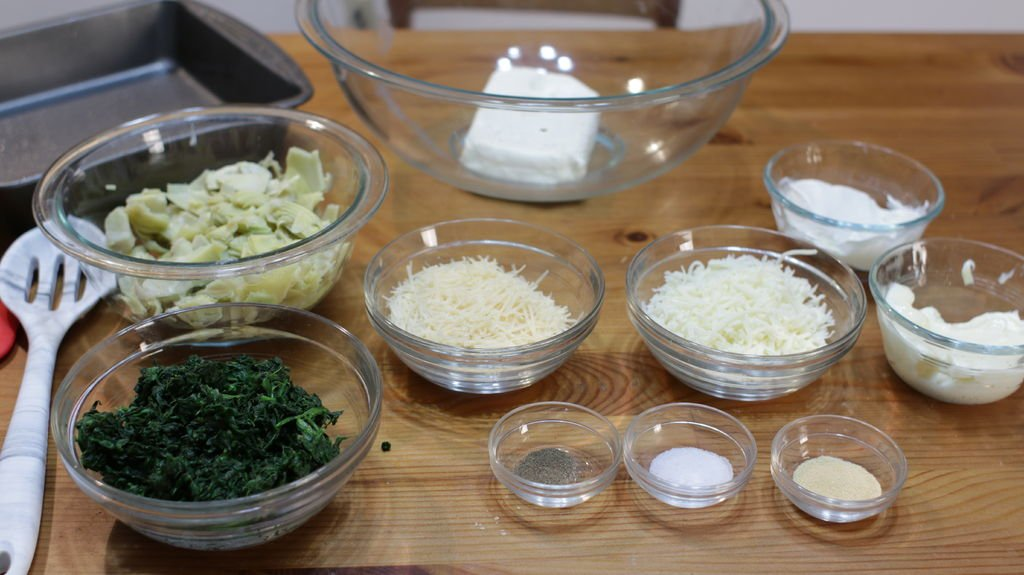 Ingredients and tools on a wooden table including spinach, artichoke, cheese, etc. all in glass bowls