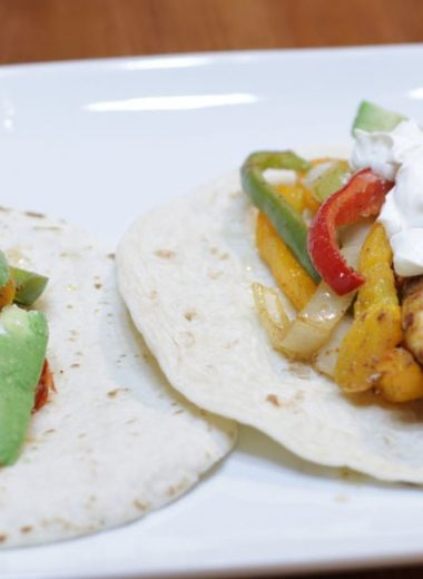 Sheet pan chicken fajitas on a white pate on a wooden table.