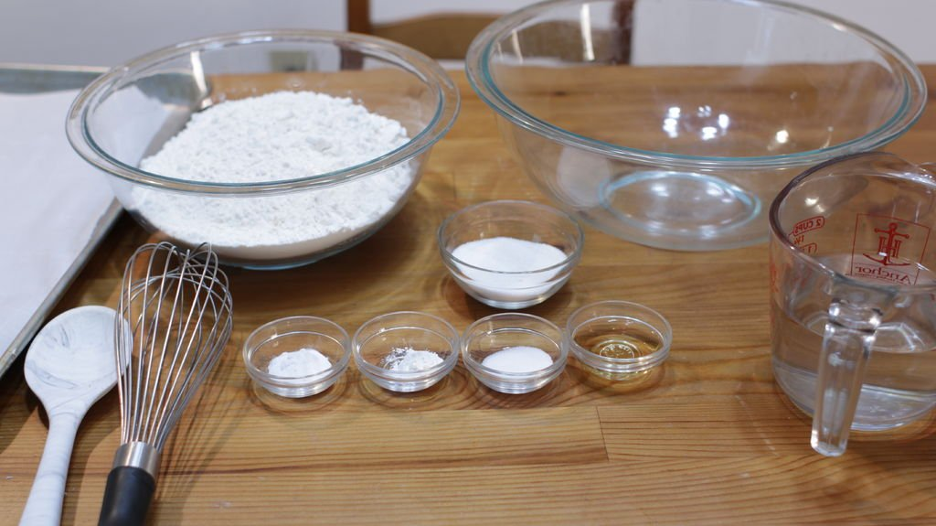 Ingredients in glass bowls on top of a wooden table, including flour, baking soda, vinegar, water, etc.