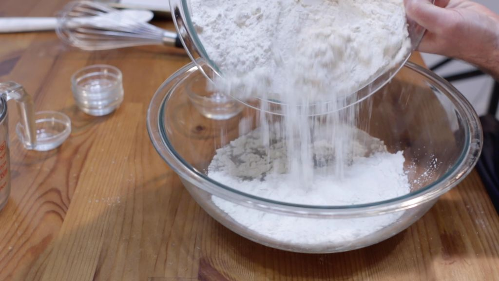 Flour with baking soda being added to a large bowl of water.