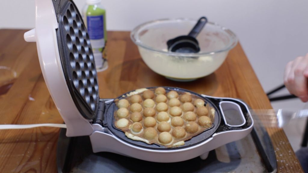 Freshly cooked bubble waffle on the iron on top of a wooden table.
