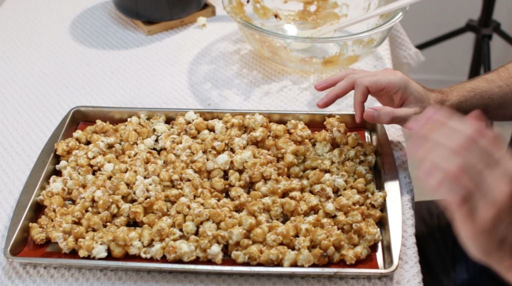 Caramel popcorn spread out on a sheet pan