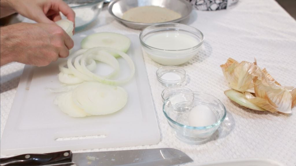 Sliced onion rings on top of a cutting board on a table with other ingredients in glass bowls