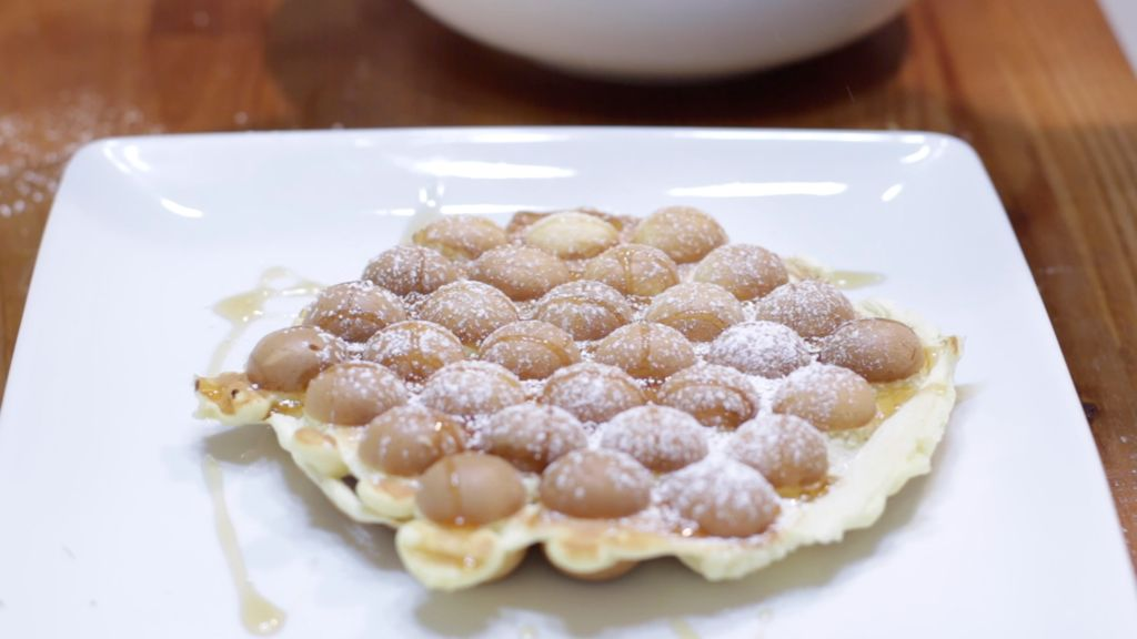 Fresh homemade bubble waffle on a white plate with syrup and powdered sugar on top.