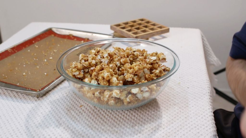 Finished caramel popcorn in a large glass bowl