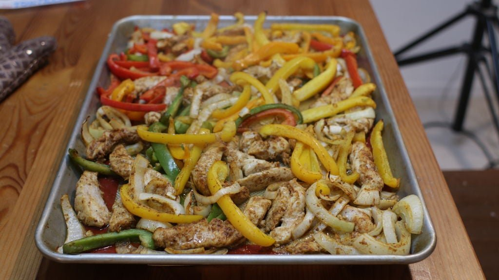 Finished sheet pan with fajitas ingredients on a wooden table.