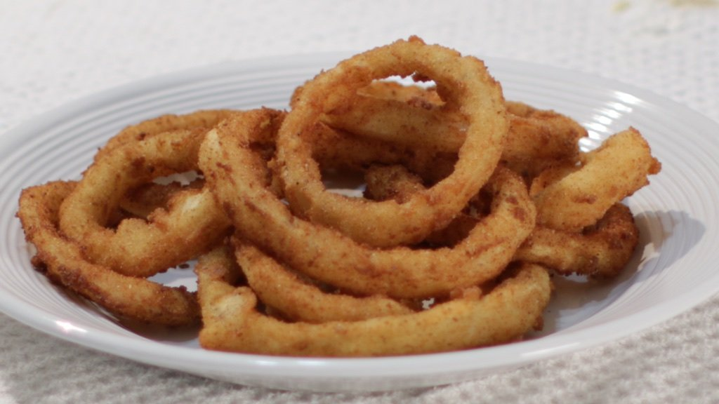 Bowl of crispy onion rings on a white plate