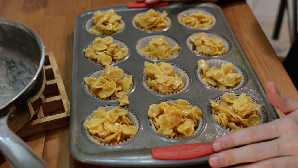Unbaked honey joys ready to go in the oven, in paper cups in a muffin pan.
