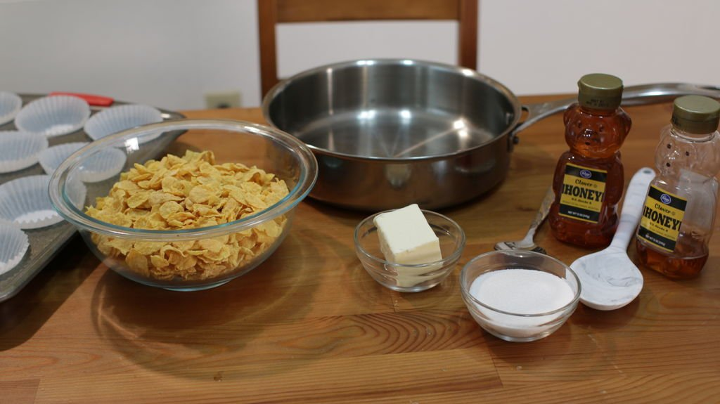 Tools and ingredients for making honey joys, including corn flakes, honey, butter, sugar.
