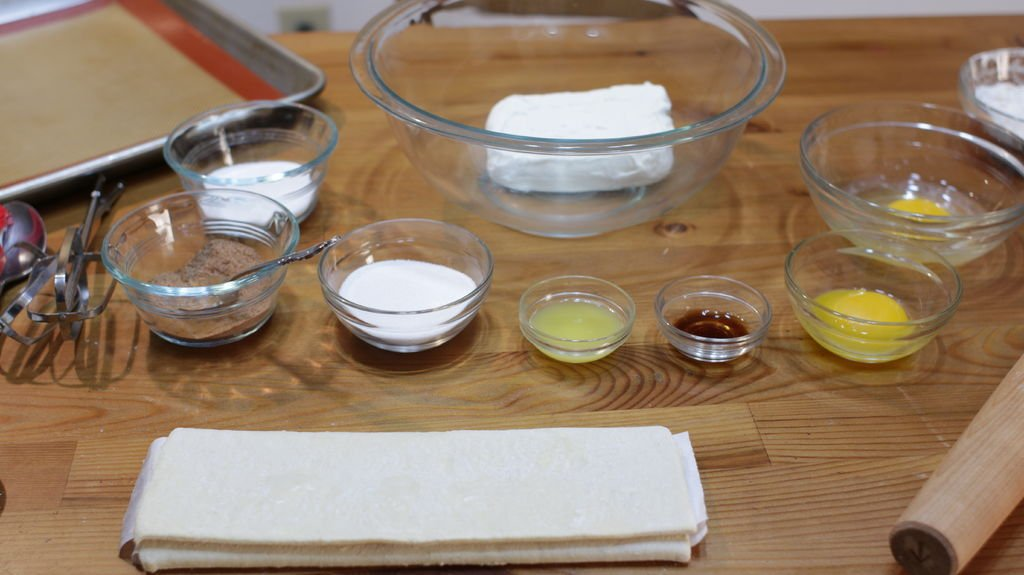 Ingredients and tools for making an easy cheese danish on a wooden table in bowls.
