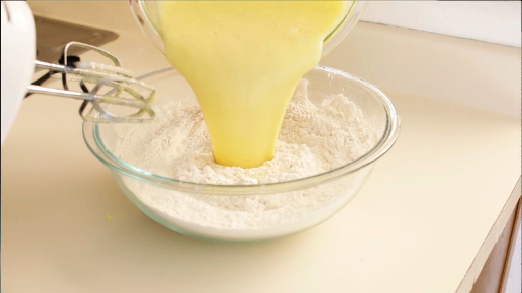 Completing the applesauce muffins batter by pouring the wet ingredients into a large glass bowl with the dry ingredients