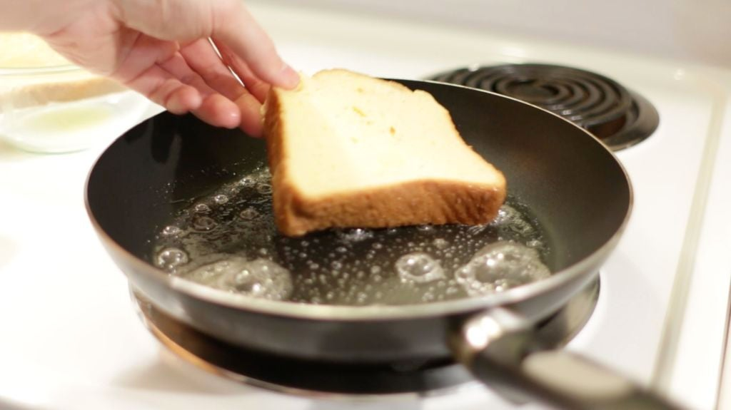 Hand dropping a piece of battered bread into a hot skillet