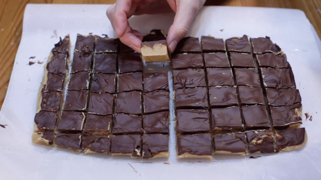 Peanut butter cup fudge cut into several squares on top of a white cutting board with a hand holding a piece.