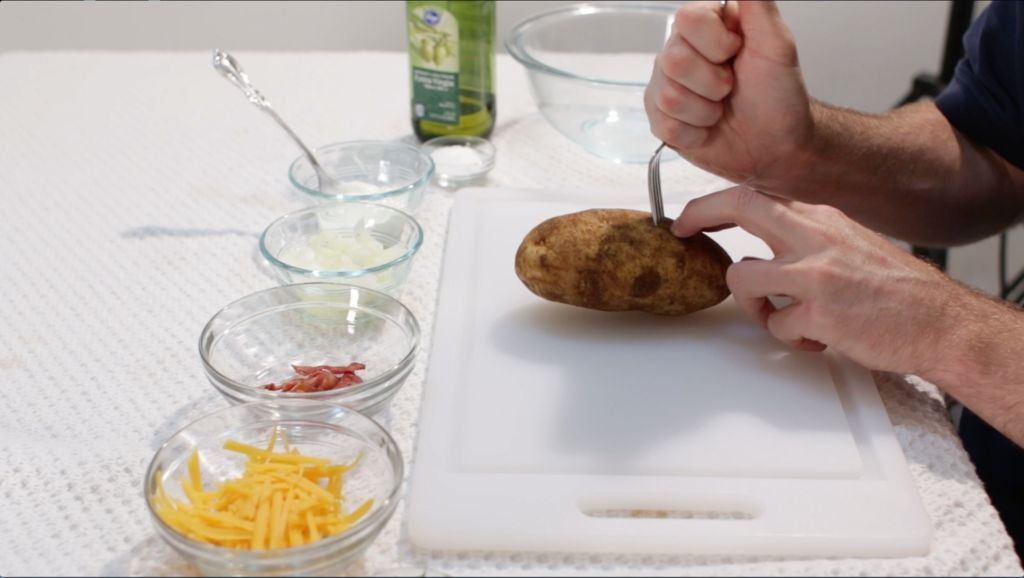 Hand poking holes in a potato with a fork