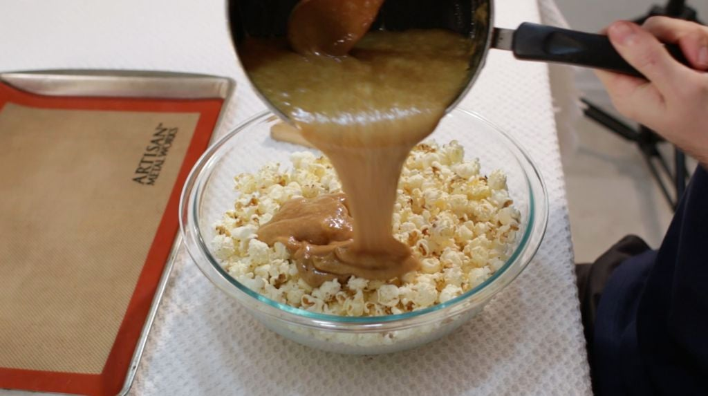 Hand pouring caramel all over the popcorn in a large glass bowl