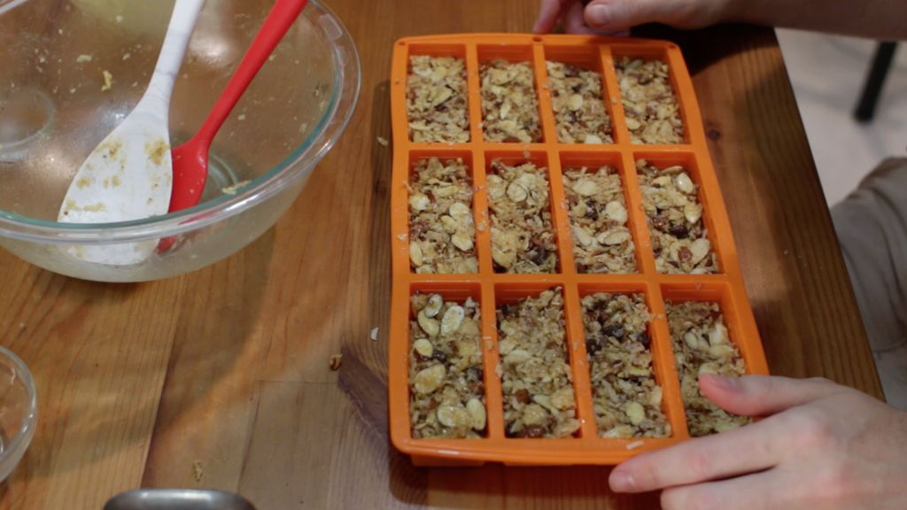 Keto granola bar mixture spread out in an orange granola bar pan on a wooden table.