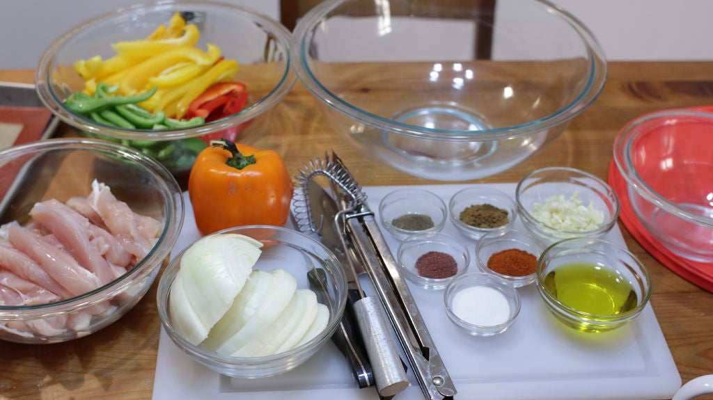Ingredients and tools for sheet pan chicken fajitas on a wooden table in glass bowls like chicken, onions, peppers, and spices.