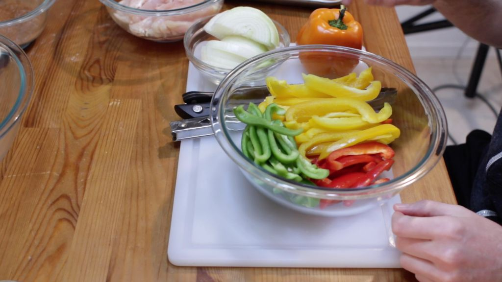 Large glass bowl of sliced bell peppers on a wooden table