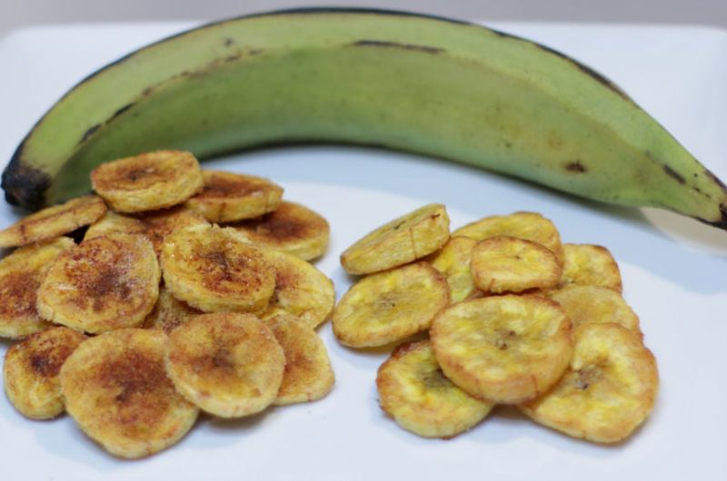 Baked plantain chips on a white plate with a green plantain