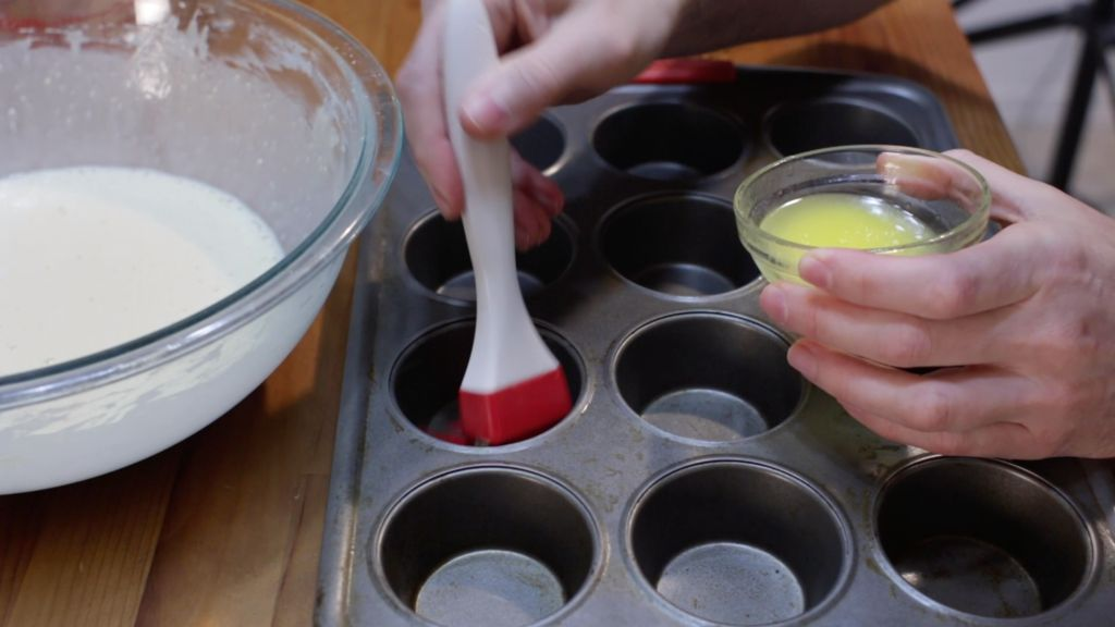 Hand basting a muffin pan with melted butter next to a bowl of popovers batter