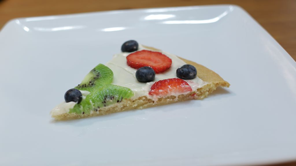 Slice of dessert pizza on a white plate on a wooden table.