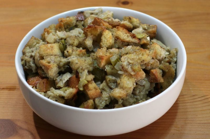 Easy classic stuffing in a white bowl on a wooden table