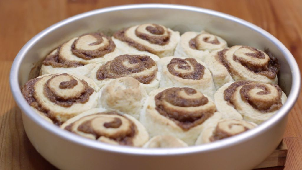 Freshly baked homemade cinnamon rolls in a round cake pan on a wooden table.
