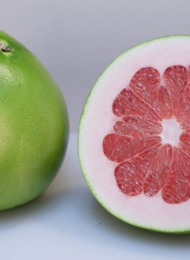 how to eat a pomelo a pomelo fruit cut in half on a white cutting board