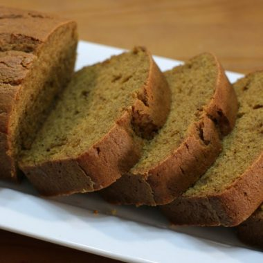 Sliced pumpkin bread on a white plate on a wooden table
